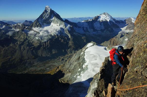 Ausgesetzte Kletterei vor fotogenem Hintergrund.