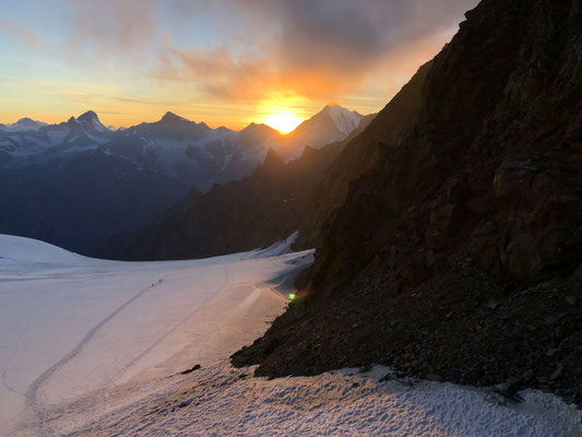 ...und die Sonnenuntergänge sind spektakulär. Ebenfalls zu sehen sind zwei Nachzügler beim Zustieg ins Biwak.