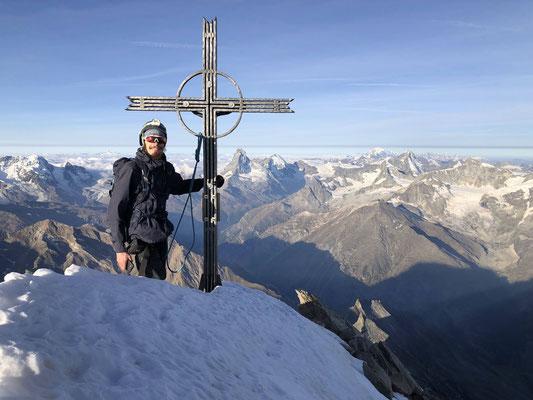 Christian und das Gipfelkreuz. Im Hintergrund Roca Nera, Breithorn, Klein Matterhorn, Matterhorn, Dent d'Herens, Mt. Blanc, Obergabelhorn, Dent Blanche und Zinal Rothorn.