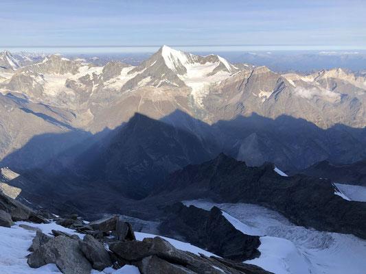 Im Westen wirft das Morgenlicht den Schatten der Mischabelgruppe aufs Weisshornmassiv.