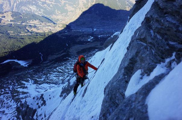 Sam in der Querung zum Schwierigen Riss, im Hintergrund der Schatten des Eigers und Grindelwald.