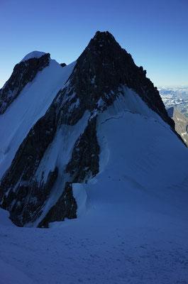 Blick zurück zur Aiguille Blanche de Peuterey, zwei Personen sind auf dem Col de Peuterey am Biwakieren.