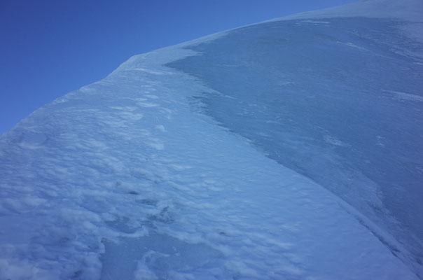 Blankes Gipfeleisfeld mit dünner Schneeauflage