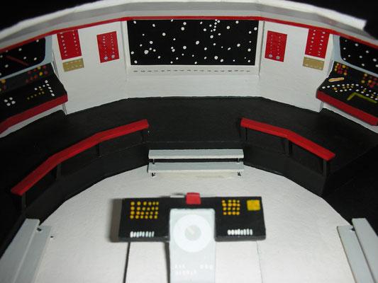 Hauptbrücke. Blick nach vorne zum Hauptschirm. Auf der linken Seite der Konsole sitzt der Steuermann (Sulu) und rechts der Navigator (Chekov).