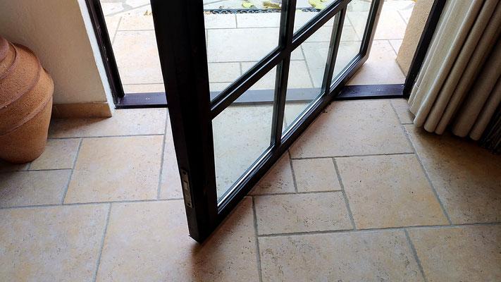 Mise en lumière d'une entrée. Création d'une porte de style atelier en acier. Détail de l'ouverture sur pivot décentré.