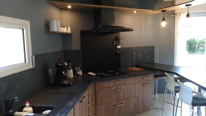 La cuisine rénovée. Plan de travail et crédence façon pierre de lave, façades chêne blanchi.