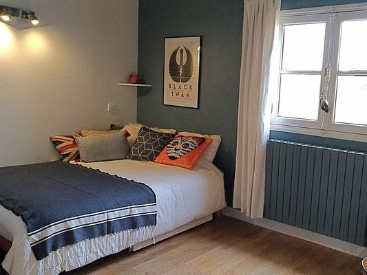 Après travaux. Chambre de jeune fille en bleu et blanc avec des coussins colorés orange, bleu et écru. Parquet en chêne blanchi.