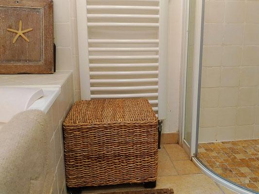 Salle de bain intemporelle en beige et blanc. Baignoire encastrée en fonte, douche italienne avec sol en travertin et porte vitrée galbée. Siège en rotin tressé.