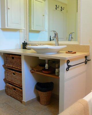 Salle de bain intemporelle en blanc et beige. Meuble vasque maçonné sur mesure avec tiroirs en rotin tressé et étagères en chêne, plan en pierre naturelle vieillie.