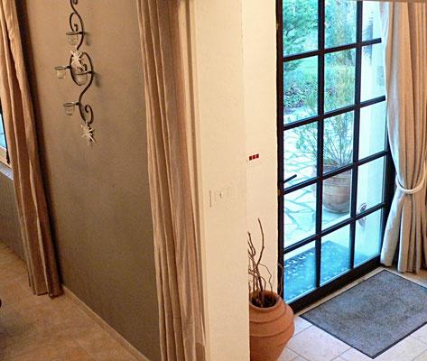Mise en lumière d'une entrée. Création d'une porte de style atelier en acier. Vue en plongée de l'escalier.
