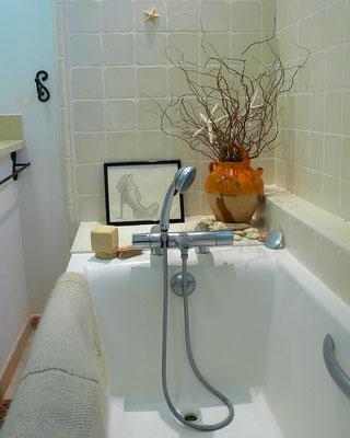 Salle de bain intemporelle en beige et blanc. Baignoire encastrée en fonte, faïences murales blanc cassé, jarre ancienne vernissée avec branchages.