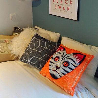 Après travaux. Chambre de jeune fille en bleu et blanc. Détail des coussins sur le lit. Coussin chat orangé en velours, Fragonard.