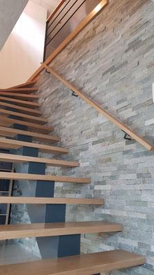 L'escalier après rénovation. Marches et rampe en chêne massif, parement mural en pierres naturelles grises.