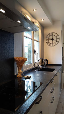 Réalisation cuisine. Façades en laque blanc lin, plan en granit noir flammé avec évier et égouttoir intégrés, sol en grès cérame façon travertin, horloge métal.