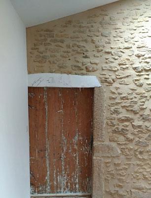 Rénovation d'une maison en pierre. Détail d'une porte remise à nu pour mettre en valeur les traces du temps sur le bois.