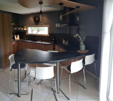 La cuisine après travaux. Plan façon pierre de lave, façade en chêne clair et peinture de crédence gris acier.