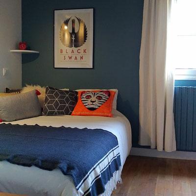 Chambre de jeune fille en bleu et blanc, parquet en chêne cérusé, spots directionnels, coussins colorés orange et bleu, rideau écru en coton épais.