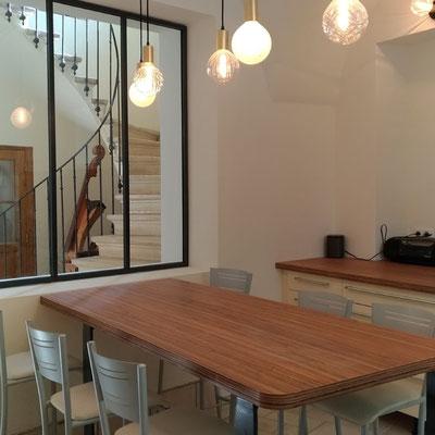 La verrière et les suspensions lumineuses assurent une grande clarté sur la table de repas réalisée sur-mesure.