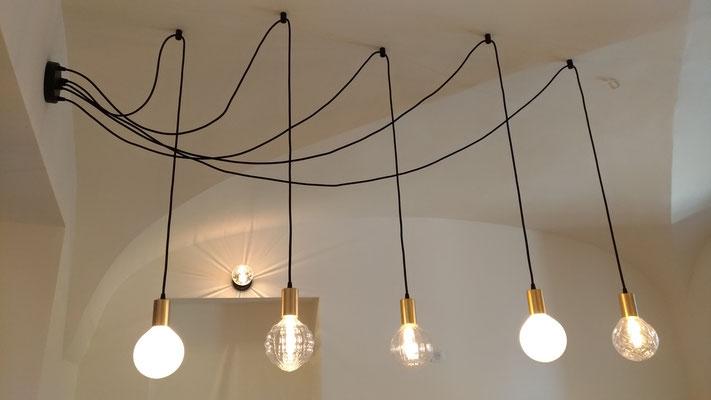 Détail des suspensions lumineuses réparties en éventail au plafond grâce à d'astucieux crochets.