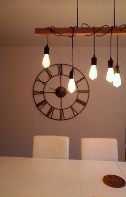 Séjour bleu cosy après travaux. Focus sur l'horloge et le luminaire industriels.