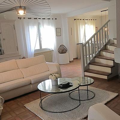 Le séjour après. Canapé en lin blanc, tables basses gigognes rondes en métal et verre, tapis blanc en laine, escalier repeint en clair, suspension Vertigo.