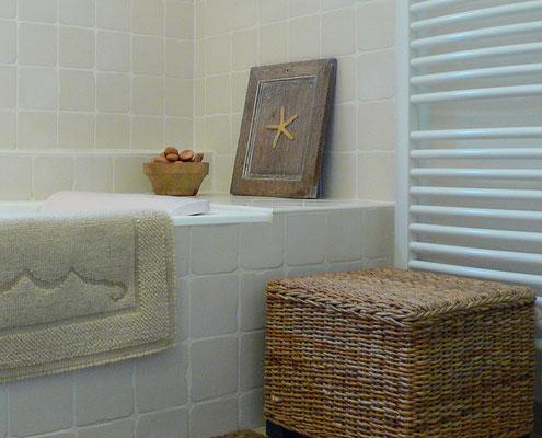 Salle de bain intemporelle en beige et blanc. Baignoire encastrée en fonte avec faïences murales artisanales, siège cube en rotin tressé, tapis en laine vierge.