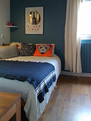 Après travaux. Chambre de jeune fille en bleu et blanc avec parquet en chêne blanchi. Des coussins colorés apportent un note tonique sur le lit blanc