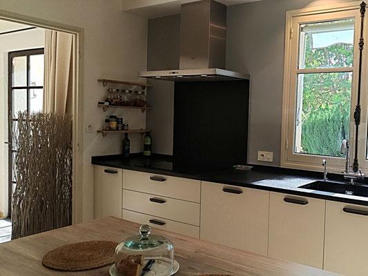 Réalisation cuisine. Façades en laque blanc lin, plan et crédence en granit noir flammé, hotte en inox brossé, fenêtre sur jardin.