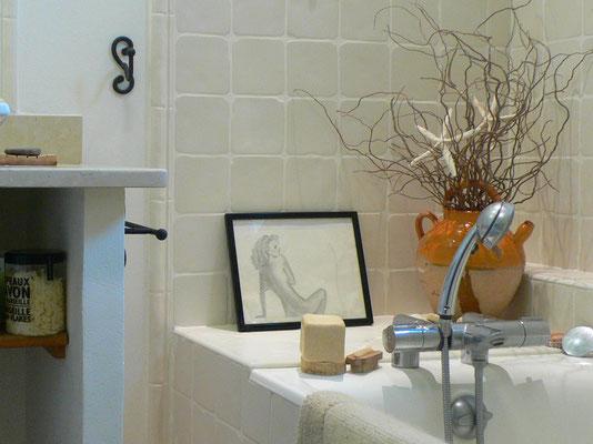 Salle de bain blanche et beige intemporelle. Meuble vasque maçonné avec plan en pierre vieillie. Baignoire avec faïences murales artisanales. Jarre vernissée.