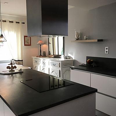 """La cuisine après. Ambiance contemporaine en noir et blanc. Mur repeint dans une teinte """"lin"""", suspensions au dessus du plan bar."""
