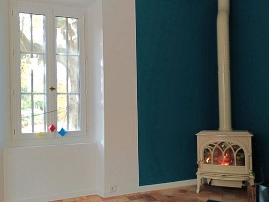 Rénovation d'une maison en pierre. Grand salon bleu et blanc avec sol d'origine en terre cuite. poêle en céramique blanche. Grande fenêtre sur jardin.