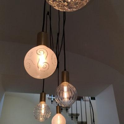 Composition de luminaires très personnalisée: chaque globe de verre est différent et monté sur une douille en laiton pour la touche rétro-chic.