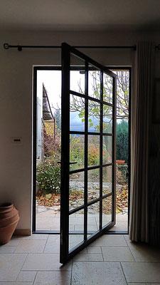 Mise en lumière d'une entrée. Création d'une porte de style atelier en acier. Détail du mécanisme d'ouverture sur pivot décentré.
