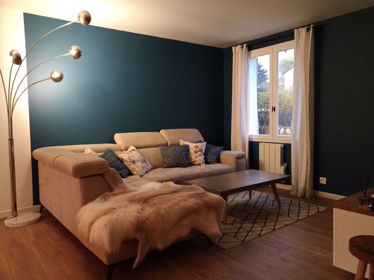 Séjour bleu cosy après travaux. Le coin salon avec peinture bleu profond mat, canapé d'angle beige clair, parquet chêne clair et tapis berbère en laine.