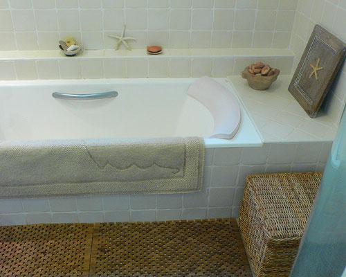 Salle de bain intemporelle en beige et blanc. Baignoire encastrée en fonte, faïences murales blanc cassé, tapis artisanal en laine , caillebotis en teck.