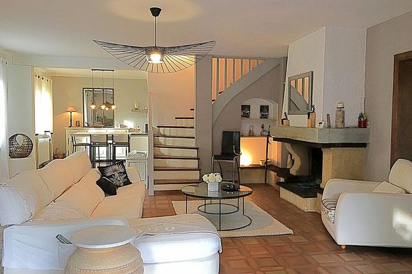 Le séjour après. Ambiance sereine et naturelle en beige et blanc. Canapé en lin blanc, suspension Vertigo Constance Guisset, tables basses rondes en métal et verre, tapis en laine blanc.