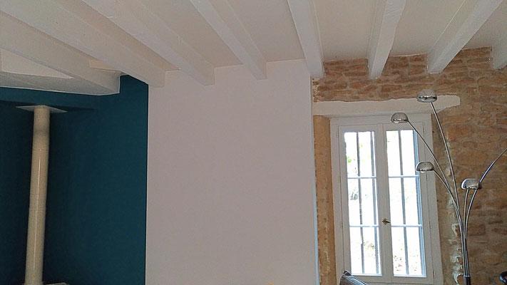 Rénovation d'une maison en pierre. Grand salon bleu et blanc avec mur en pierre apparente. Plafond et poutres peints en blanc et beige.