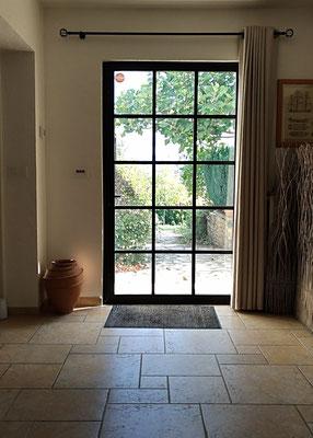 Mise en lumière d'une entrée. Création d'une porte de style atelier en acier. Rideaux épais en lin et viscose, jarre artisanale.
