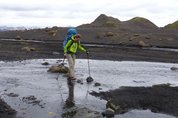Trockenen Fusses auf die andere Seite von Stein zu Stein hüpfend. Als Unterstützung dienen Trekkingstöcke.