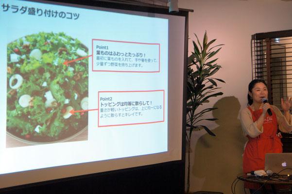 サラダの盛り付けのレクチャーをする岩渕さん