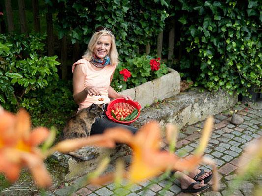"""Kathrin Schirmer freut sich über die selbstgezogenen Geranien, genießt die Kirschen aus eigener Ernte und """"Tequila"""", ihre Katze, findet alles einfach nur """"schnurrig"""" schön."""