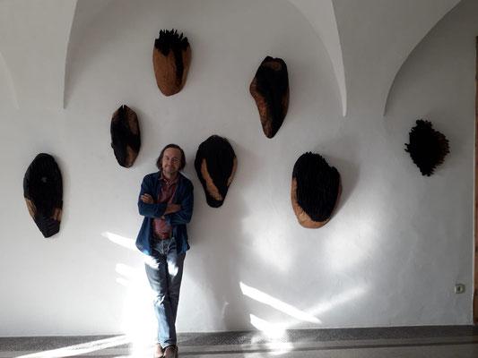 Einblick in die Ausstellung 'Zwischen Bild und Skulptur' im  Schloss Ebenau, 2019, Johann Feilacher vor seinen Masken ©Galerie Walker