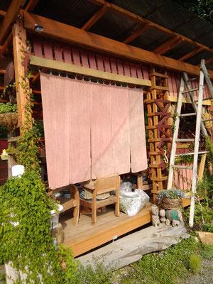 Nさん宅の玄関前には、手づくりの小さなあずまやが。のれんは、ベンガラと柿渋染め。