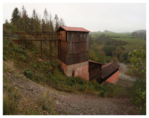 """Blick von der Halde auf die Aufbereitungsanlage, links die wieder errichtete Brücke (""""Rennbahn"""") vom Schacht zur Aufbereitung"""