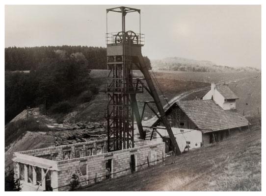 Errichtung des stählernen Fördergerüstes am Schacht Martenberg, rechts das Maschinenhaus (Quelle: Darstellung im Bergbaumuseum Grube Christiane)