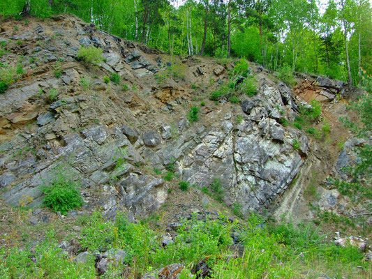 Die farbenprächtigen schrägeinfallenden Kalksteinschichten an der oberen südöstlichen Bruchwand.