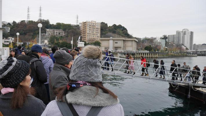 小雨降る中、多くの人が船を待ちます。