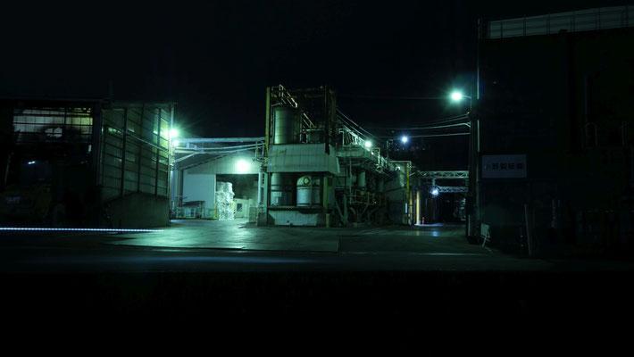 春日製紙工業の川向いにある工場。白い点々のラインは、通りかかった自転車のライトです。