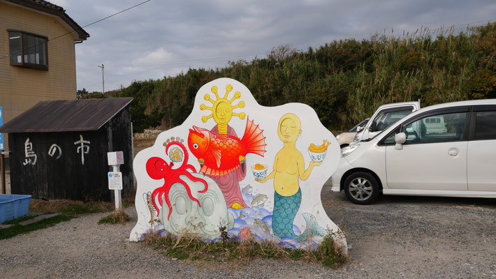 『佐久島歓迎 地福開円満』。西港付近にある、顔出しパネルです。オブジェの顔部分が開くようになっています。