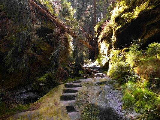 Felsige Engstelle im Brückengrund. Links die Felswand ist abgemeißelt, darunter eine ausgemeißelte Wasserrinne.